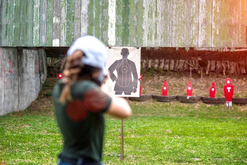 Девушка в тире стреляет по мишеням