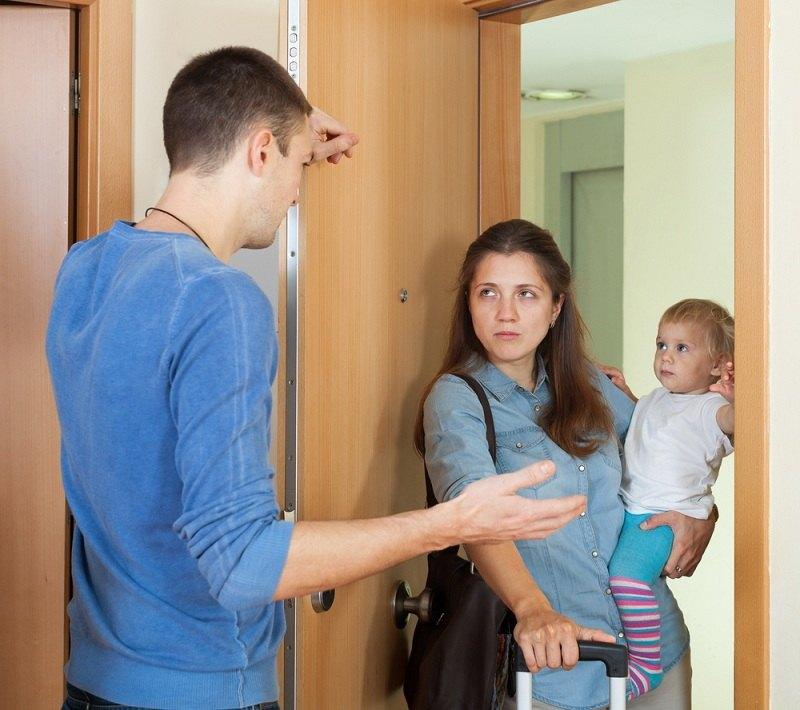 Супруги ругаются у входной двери, женщина держит ребенка