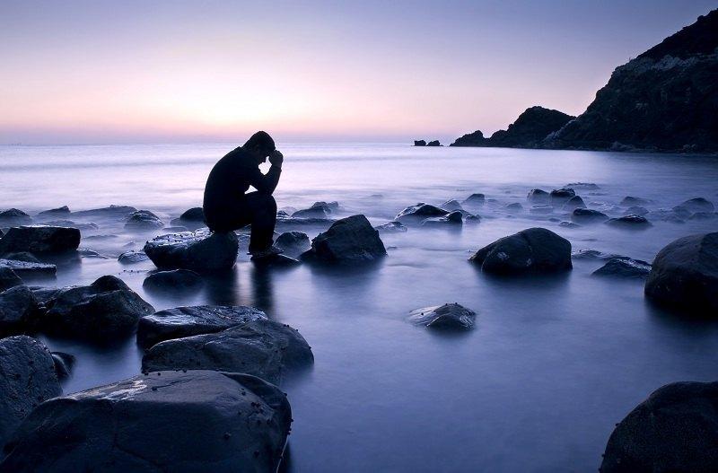 Мужчина сидит на камнях и переживает по поводу жены и ее любовника
