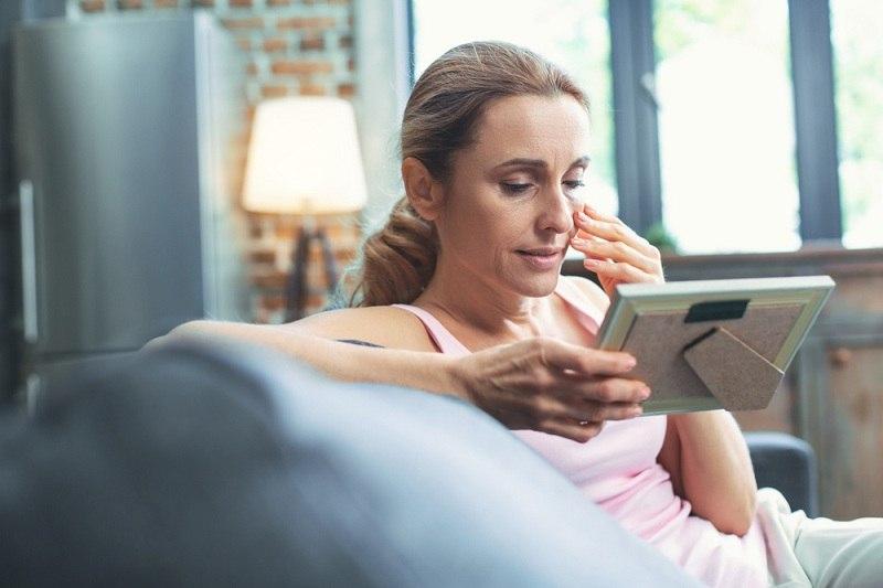 Расстроенная женщина смотрит на семейную фотографию после измены мужа