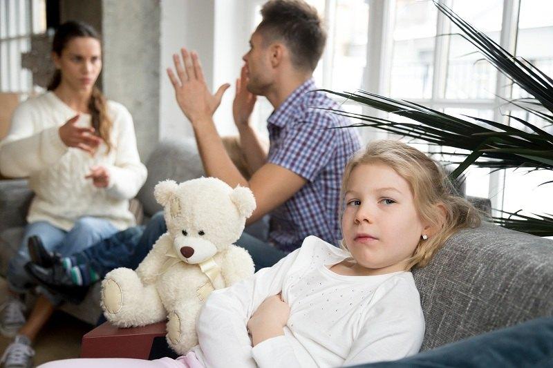 Девочка с игрушечным мишкой наблюдает за поведением родителей после развода