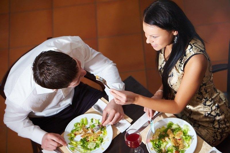 Влюбленная пара сидит за обеденным столом