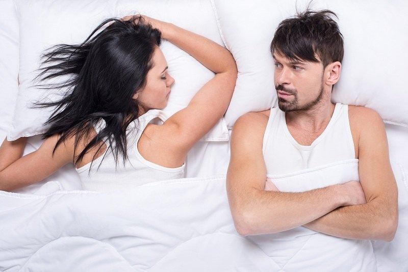 Мужчина лежит в кровати, а жена спит