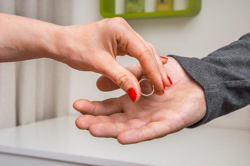 Женская рука отдает обручальное кольцо мужу