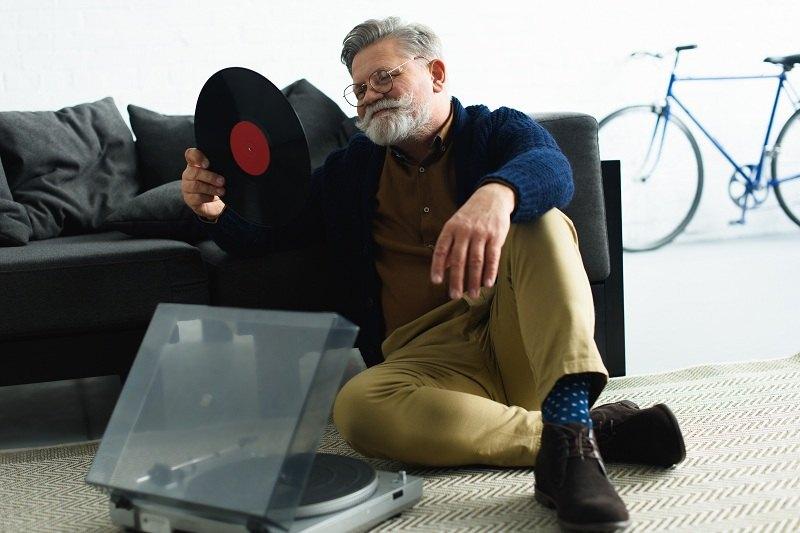 Пожилой мужчина после развода в 60 лет смотрит с ностальгией на любимую пластинку