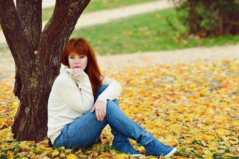 Девушка сидит на траве и думает что делать с мужем, если люблю любовника