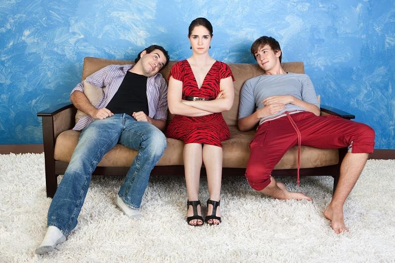 Женщина сидит на диване с мужем и возлюбленным