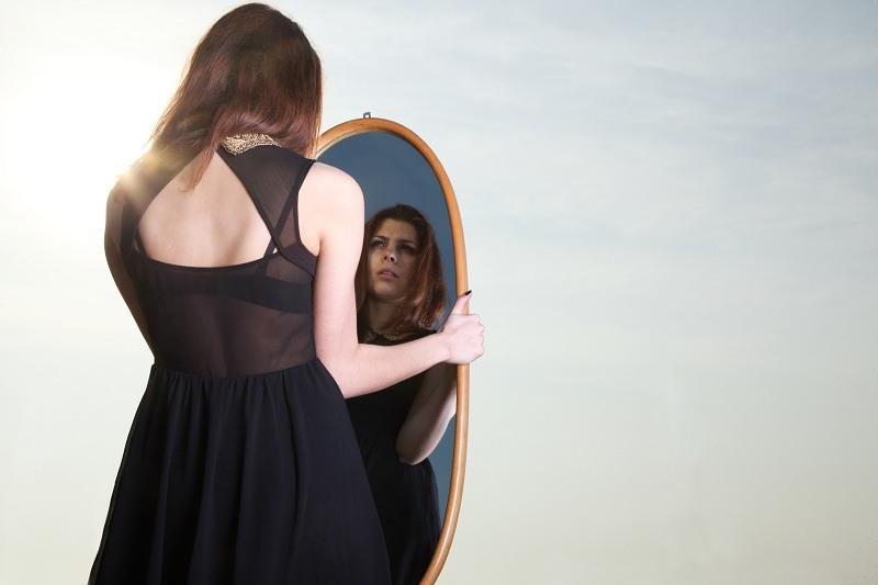Девушка смотрит в зеркало - больно вспоминать о том что ей изменили и предали
