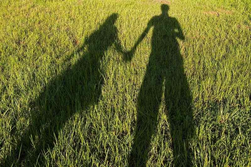 Тень мужчины и женщины, которые держаться за руки