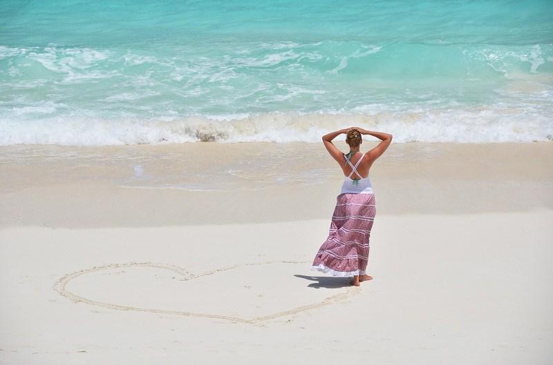 Задумчивая девушка смотрит в океан - у нее остыли чувства к парню