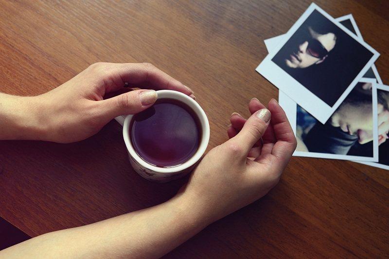 Женщина с чашкой кофе тяжело переживает развод