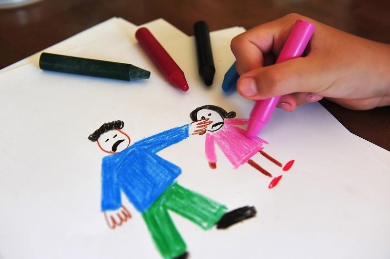 Ребенок рисует на бумаге папу и маму