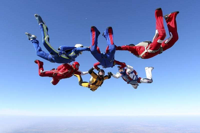 Спортсмены прыгают с парашютом и летят в небе