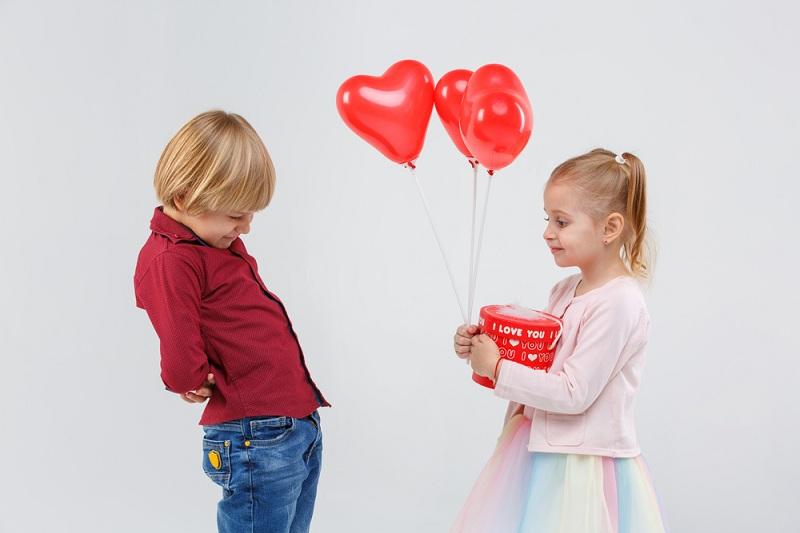 Девочка дарит мальчику подарок - это первая любовь