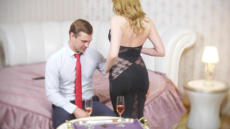 Любовница с мужчиной пьют шампанское