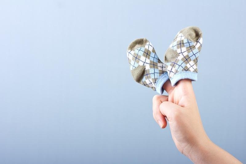 Женская рука с носочками - символ счастливой семьи