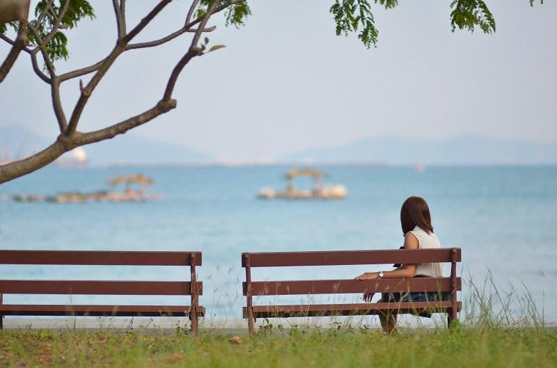 Женщина смотрит на море и скучает о бывшему супругу после развода