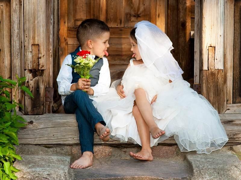 Девочка и мальчик играют в молодоженов