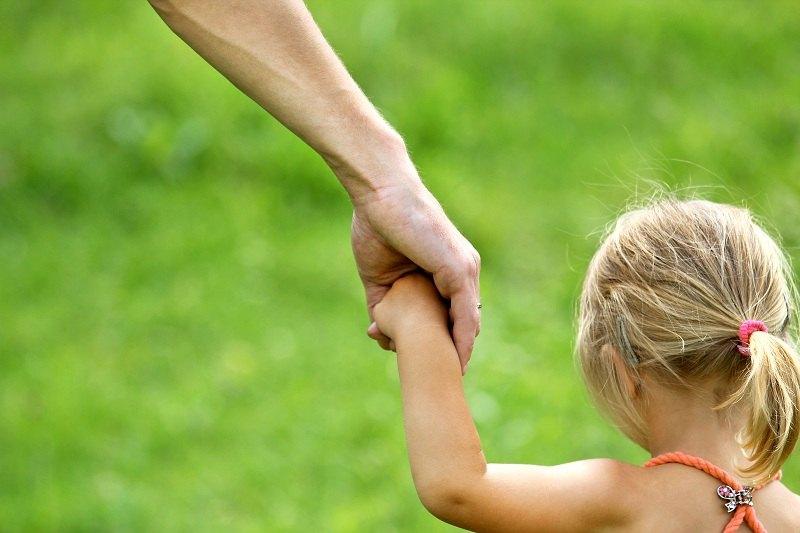 Мужская рука держит ребенка за руку