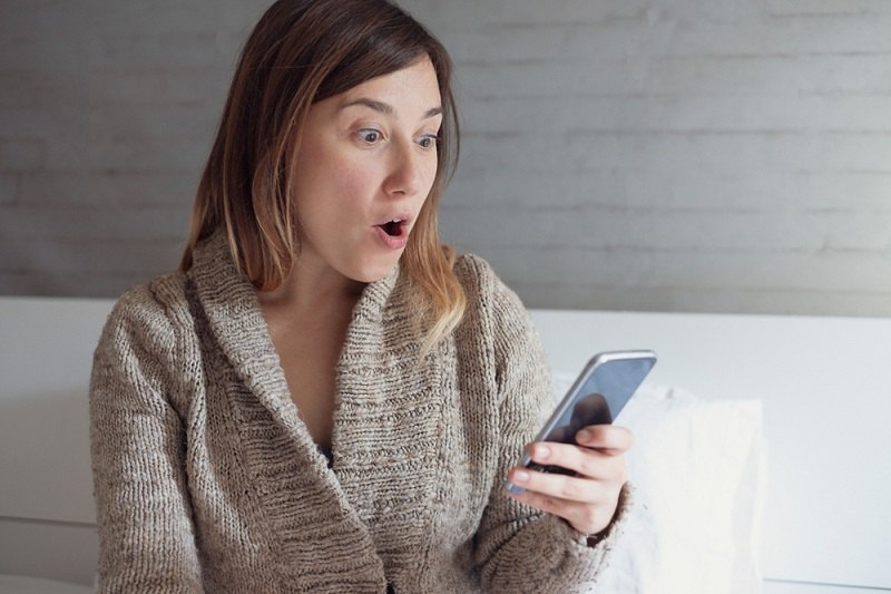 Девушка читает смс сообщения на телефоне парня и понимает, что он ей изменил