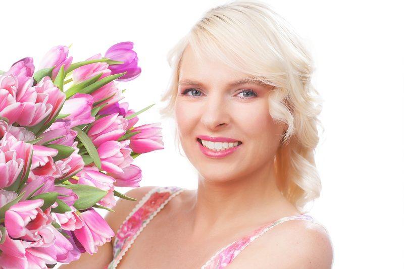 Улыбающаяся женщина с красивыми цветами пережила измену своего мужа и вернулась к счастливой жизни