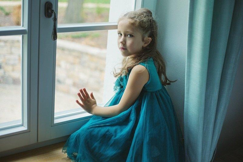 Грустная девочка сидит у окна узнав новость, что ее родители разводятся