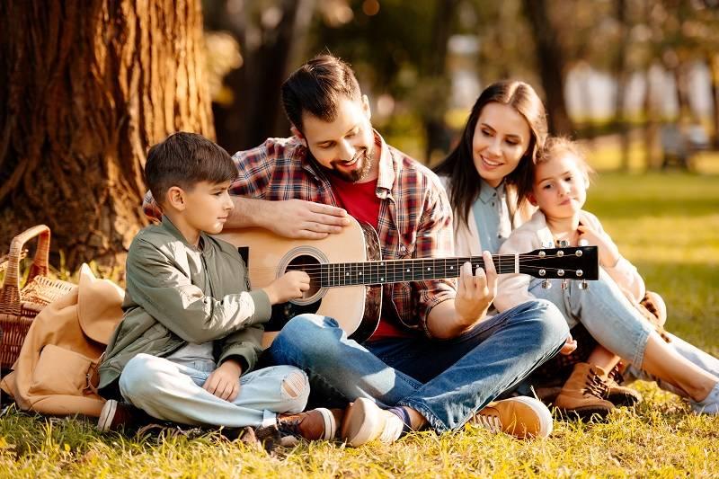 Семья на пикнике, отец играет на гитаре, жена и двое детей слушают его песни
