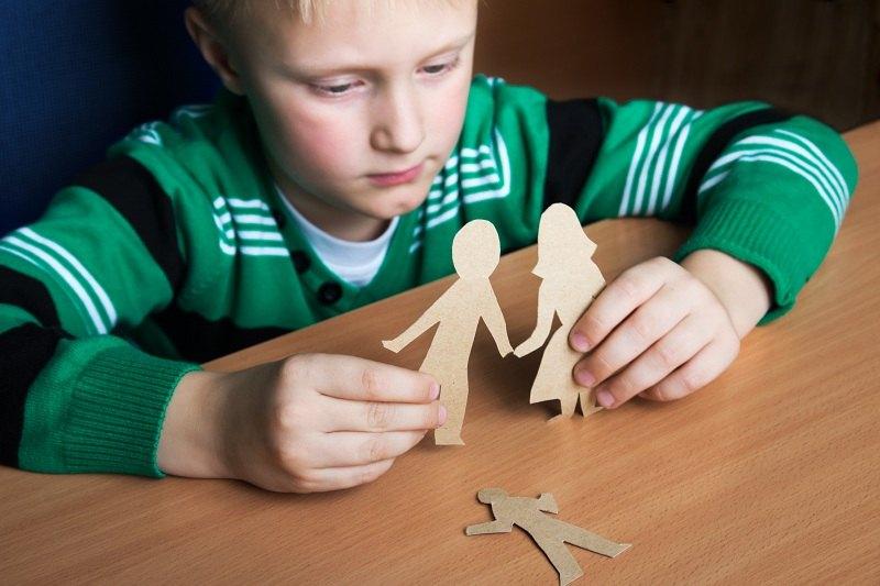 Мальчик играется фигурками родителей, которые расторгают брак