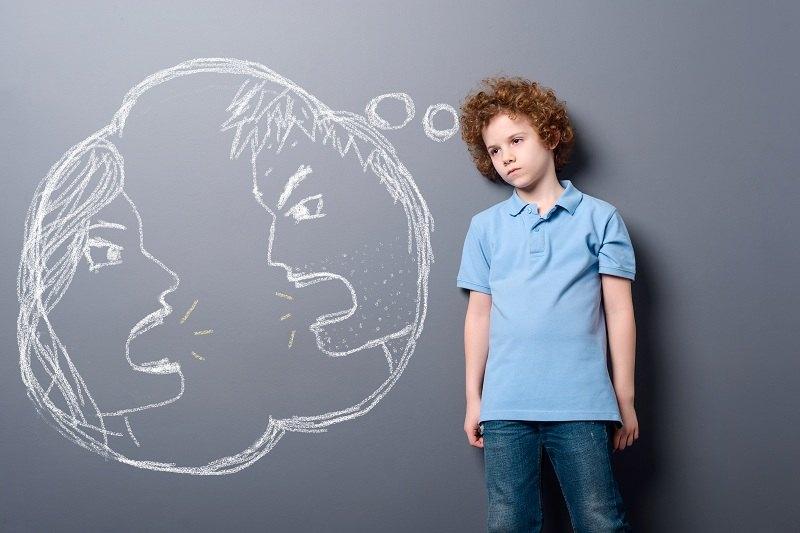 Мальчик грустит на фоне ссор своих родителей