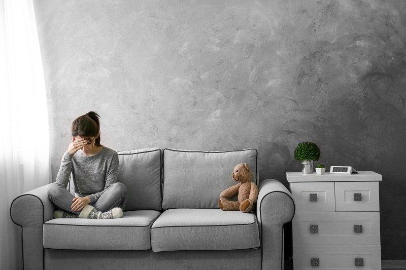 Девочка сидит на диване со своим игрушечным мошкой и плачет из-за развода родителей