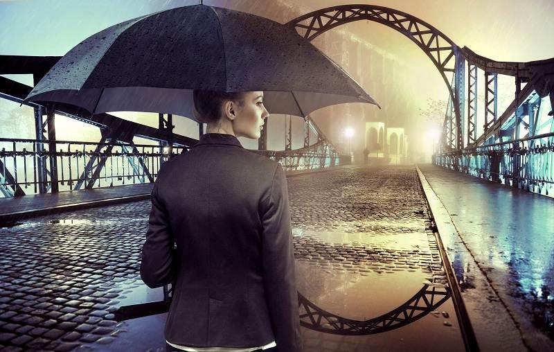 Женщина стоит на мосту под дождем и решилась инициировать развод со своим мужем