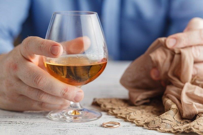 Мужчина со стаканом виски и обручальным кольцом переживает кризис отношений со своей женой