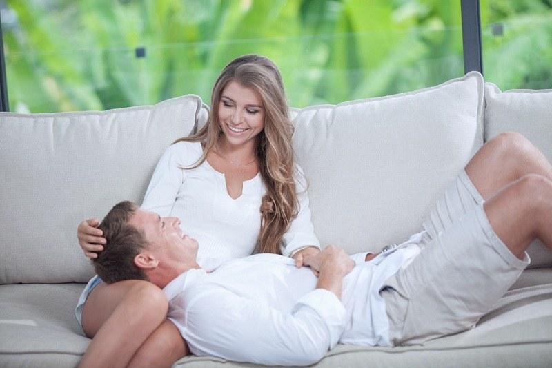Женатый мужчина с любовницей кокетничают на диване