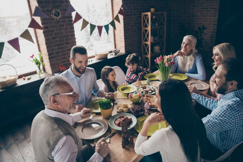 За семейным столом сидит семья и родители супруга, с которыми жена конфликтует