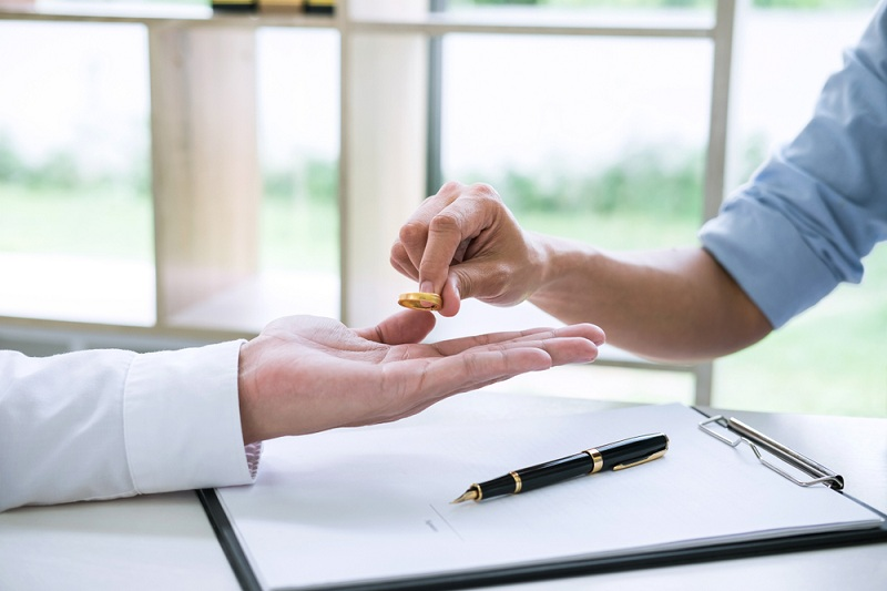 Женская рука отдает мужу обручальное кольцо - это конец отношениям