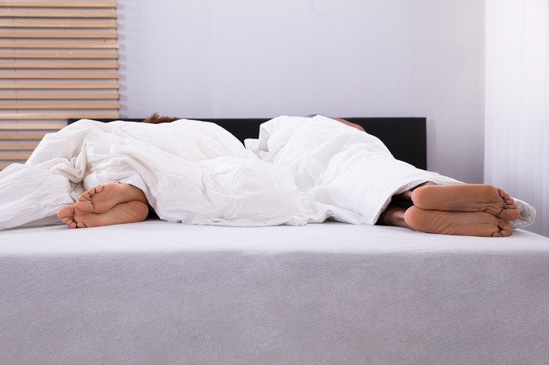 Супруги спят на кровати порознь